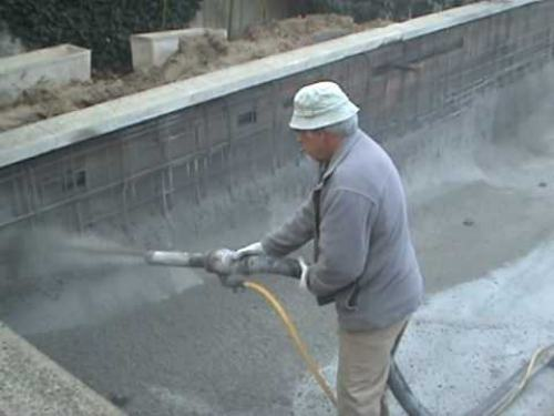 worker pouring concrete into a swimming pool