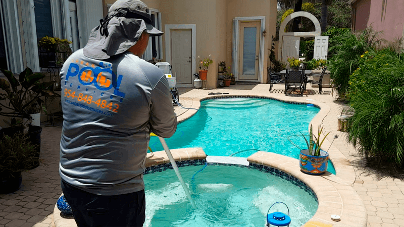 Urban Pool Services certified personnel cleaning a pool